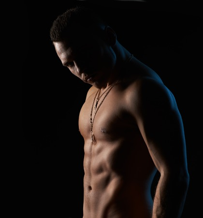 37311449 - strong sexy man on a black background