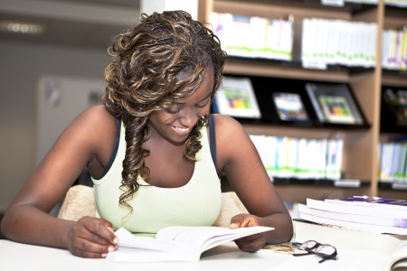 pretty teenager black african college student girl smiling and reading a book in the library - making me time