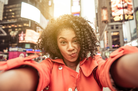 50428377 - young american woman taking selfie in new york, time square