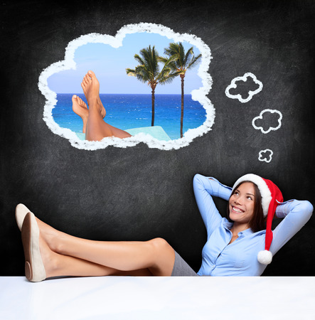 32327659 - young woman dreaming about tropical holidays while sitting with the feet over the desk and wearing a santa hat