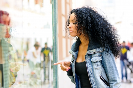 17658109 - portrait of an attractive black woman, afro hairstyle, looking at the shop window
