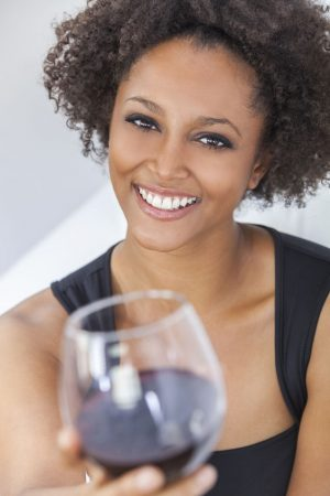 Will You Be My Valentine? 65707932 - a beautiful happy mixed race african american girl or young woman wearing a black dress and drinking red wine at home