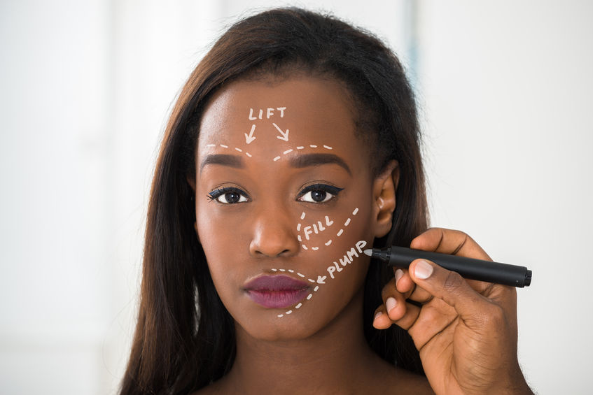 MelanMag - FaceValue - 55429561 - close-up of person's hand drawing correction line on young african woman's face