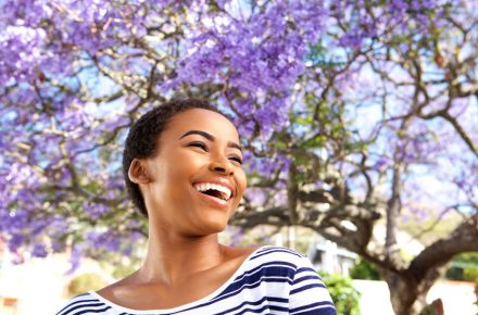 Refresh your life with a good spring clean 71517809 - portrait of attractive young black woman laughing outdoors by flower tree