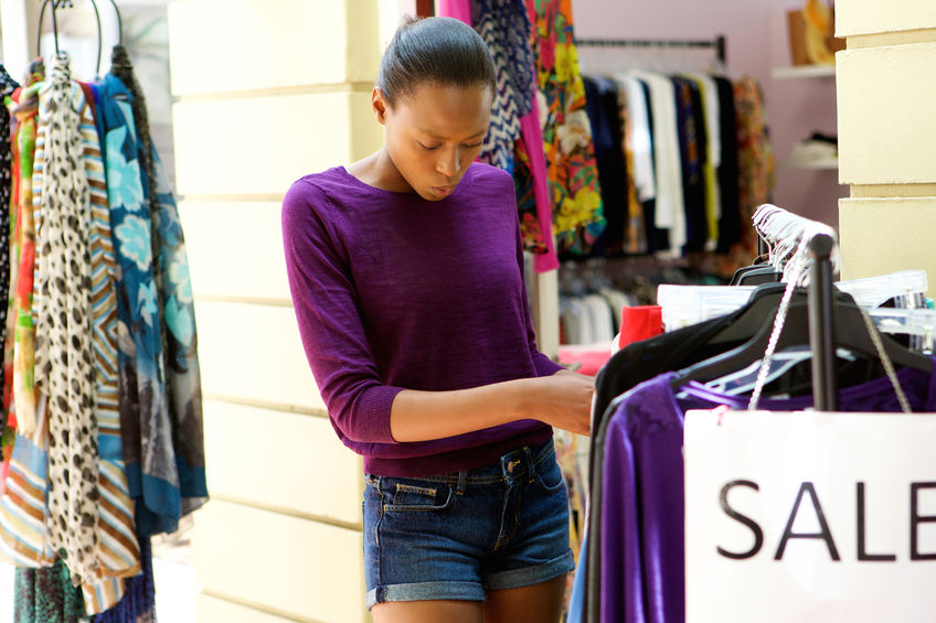 The case of the £1,000 shopping habit! - 53472541 - portrait of young african woman looking at clothes to buy at shop