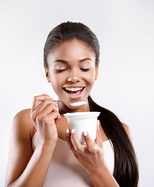 stay healthy. young mulatto girl is isolated on background. she is eating yoghurt - 4 Food Truths and Myths Go Head-to-Head