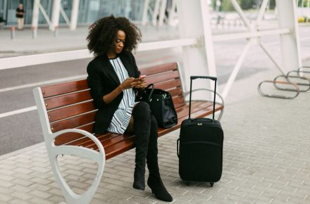 59945331 - beautiful african american woman with suitcase using smartphone while sitting on bench near airport - Seven things to remember about the 'carry on' ban on large electronic devices