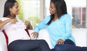 24446491 - woman visiting pregnant friend at home How to keep your friends after motherhood