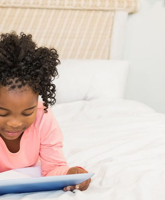 "48149968 - young girl using tablet on bed at home ""Put down the iPad and go play outside"" say parents to tech-obsessed kids"