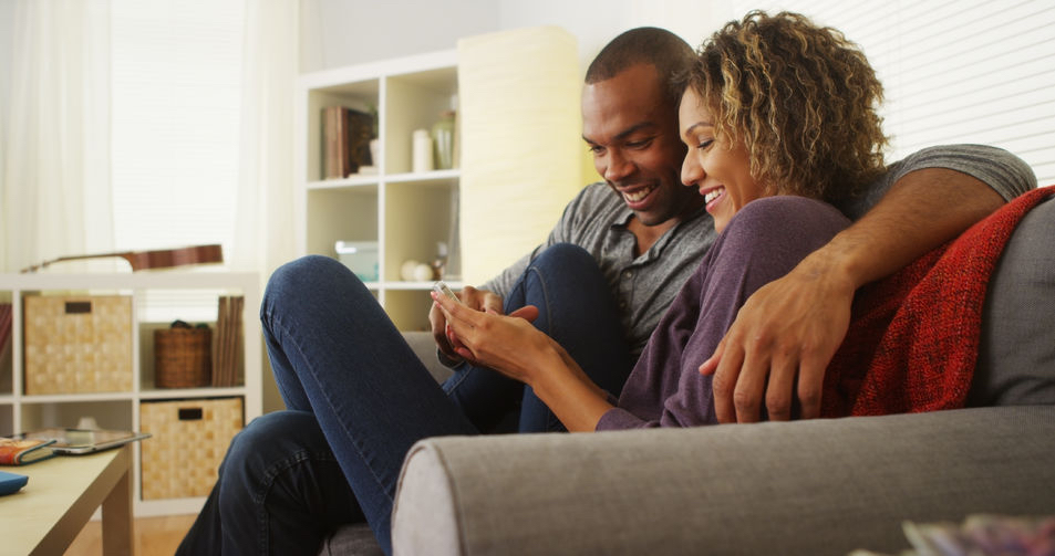 33805927 - black couple using smartphone together on couch Apps to help your love life: Infographic