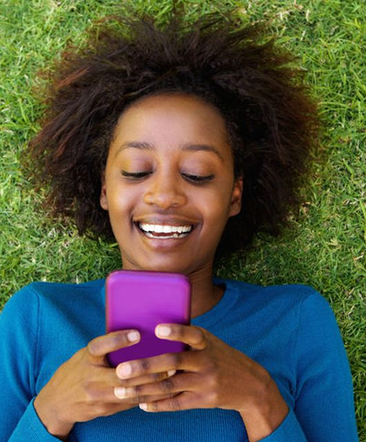 53357923 - portrait from above of a smiling african woman lying on grass looking at cell phone 8 Essential apps for a healthy and happy life
