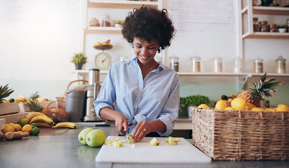58560741 - indoor shot of attractive young woman chopping fruit to make a fresh juice. african female working at juice bar. What's stopping you from getting your five a day?