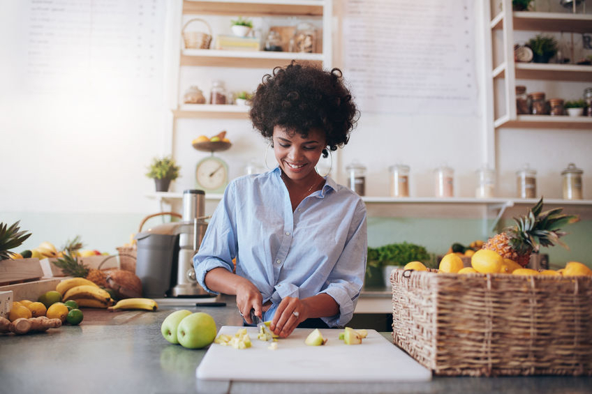What's stopping you from getting your five a day? 58560741 - indoor shot of attractive young woman chopping fruit to make a fresh juice. african female working at juice bar.