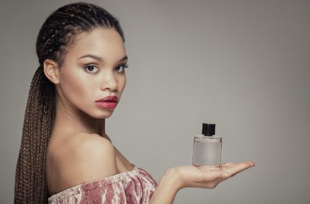 Whose scent is it anyway? - 70739566 - beauty portrait of young african american girl holding bottle of perfume, looking at camera.
