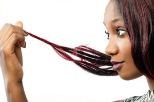 Are hair dyes and relaxers increasing the risk of breast cancer? 55596654 - macro close up portrait of young african woman looking at dry edges of dyed hair.isolated on white background.