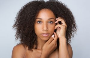 38346904 - close up portrait of an african beauty woman with curly hair posing with hands by face - Natural hair movement drives sales of shampoo skyward