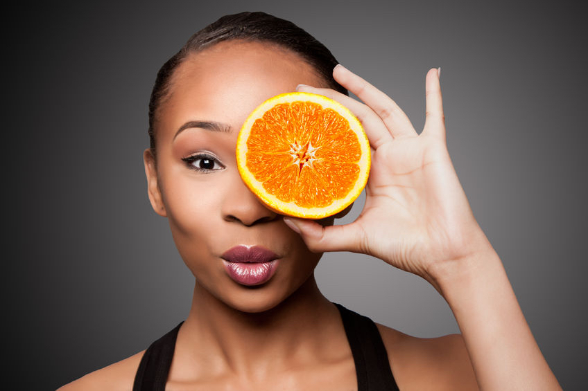 How a Vitamin C boost can be just what your skin needs this winter 74368223 - beautiful healthy happy black asian woman holding delicious orange mandarin fruit in front of eye.