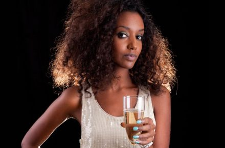 10985494 - young beautiful african american woman holding a glass of champagne The real benefits of why we should reduce our booze intake