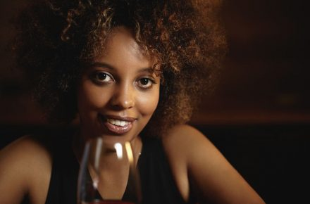 63035657 - people and leisure. attractive african female with mysterious smile and healthy shiny skin, holding glass of red wine, sitting against wooden wall background with copy space for your content Seven Alternative things to do in London this Valentine's Day